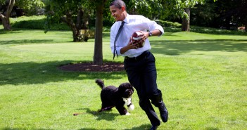 President Barack Obama, with the family dog Bo, playing football on the South Lawn of the White House May 12, 2009.