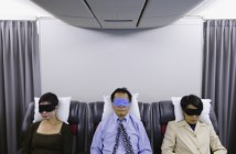 3 passengers trying to sleep during an airplane flight