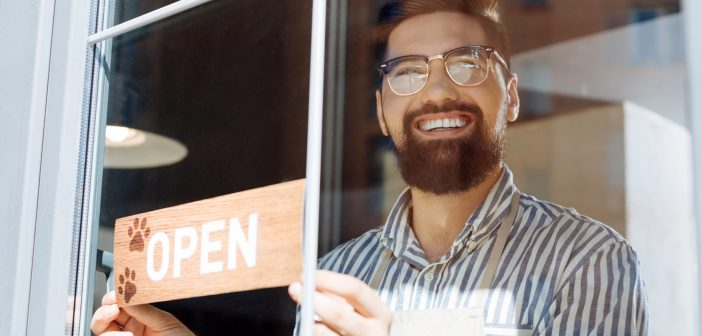 smiling man placing an open sign on a cafe window
