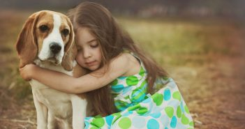 little girl hugging her beagle dog
