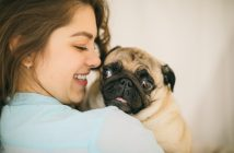 girl hugging her pug dog