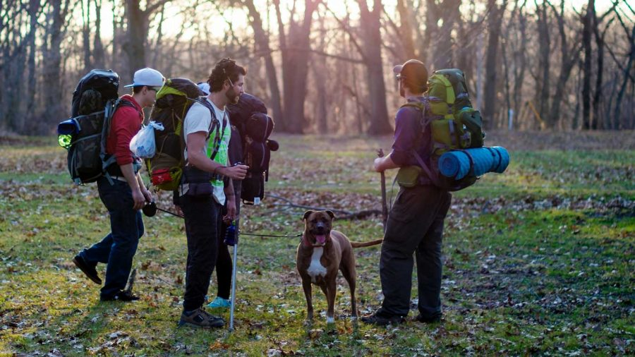 group of men and a dog hiking