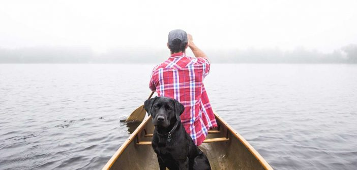 man and dog in a boat