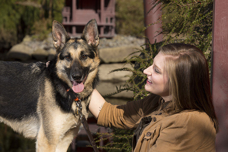 a woman looking at her well-behaved german shepherd